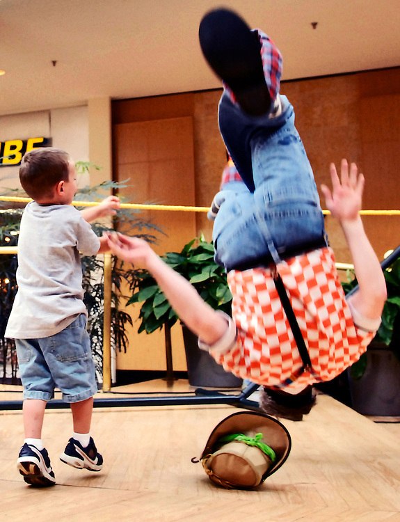 (Staff Photo by Matt Roth)..In his act, Greg May incorporates physical comedy with crowd participation as is demonstrated by the apparent flip three-year-old Mickey Mansfield, from White Marsh, executes during May's performance to a sizable crowd of children and parents at White Marsh Mall's Family Fun Day Tuesday morning June 20, 2006. ..