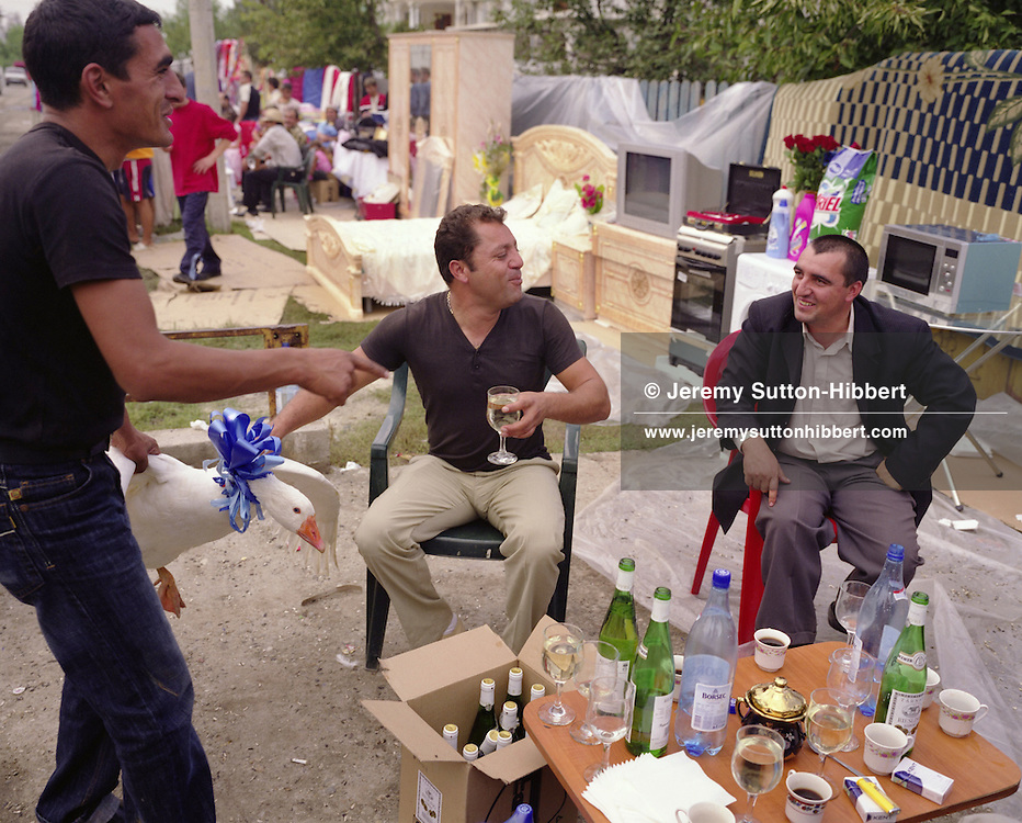 """Men sit drinking surrounded by goods which constitute the dowry of 14 year old Garoafa Mihai on the day of her wedding to 13 year old Florin 'Ciprian' Lulu, in the village of Sintesti, in Romania, Sunday, Sept. 24, 2006.  The men hold a goose decorated with a blue ribbon, as a gift to an old women from whom many years previously they had stolen a goose. For the wedding of Garoafa and Ciprian 100 pigs, costing approximately 30,000 USD, were slaughtered. Garoafa wore a gold """"salbe""""- a necklace of gold Franz Josef coins, worth an estimated 30,000 USD. The Kalderari roma of Sintesti are by tradition metal workers, originally making alcohol stills, pots and pans, but now dealing in scrap metal. The large profits from their business have enabled them to build large houses in the village of Sintesti, 20km from Bucharest, and to invest in fast, Western brand name cars such as BMW's, Mercedes and Porsche."""