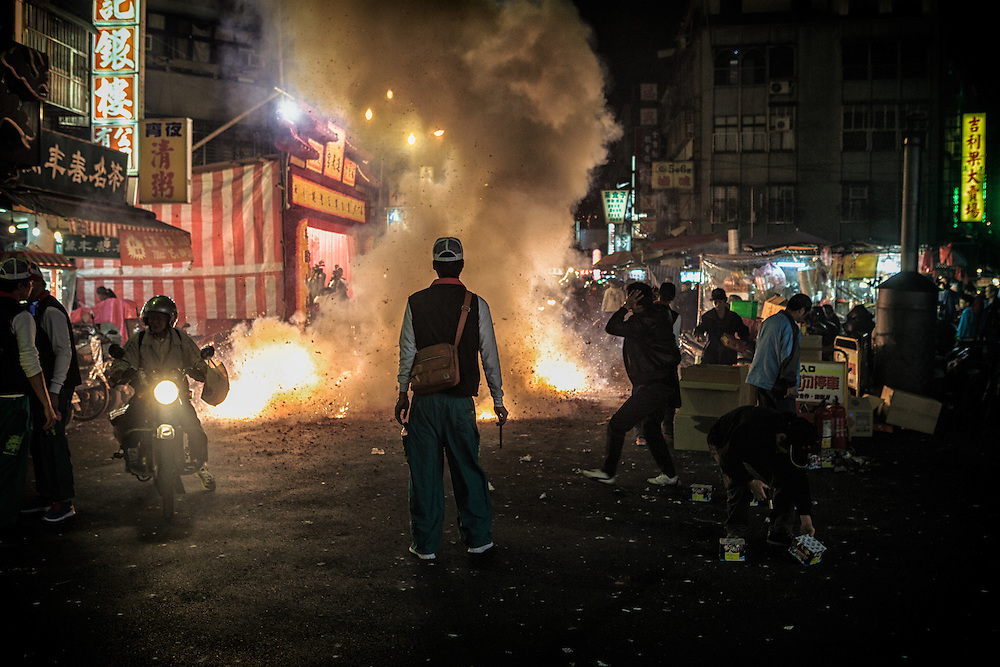 Firecrackers are let off on a city street during a religious festival.