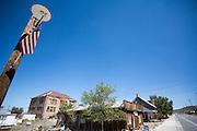 Linksachter staat de Goldfield Highschool uit 1907. Het verkeert nu in erbarmelijke staat, er zijn plannen om het gebouw te restaureren. Rechts vooraan staat de garage waar Dahlstrohm begonnen is voor hij verhuisde naar een nieuwe lokatie. Goldfield, Nevada, is een bijna verlaten ghost town in Esmeralda County, gelegen aan de State Route 95. Tussen 1906 en 1910 was Goldfield de grootste plaats in de Amerikaanse staat Nevada met meer dan 20.000 inwoners. Momenteel leven er tussen de 200 en 300 mensen. Het plaatsje is groot geworden door de vondst van goud in 1902. Vanaf 1910 daalde het aantal inwoners snel en in 1923 is een groot deel verwoest door een brand. De overgebleven huizen zijn grotendeels verlaten, maar worden nog altijd onderhouden door de inwoners. Daarmee wordt de geschiedenis van de het plaatsje bewaard.<br /> <br /> Rear left is the Goldfield High School in 1907 and is now in a pitiful state, there are plans to restore the building. Front right is the garage where Dahlstrohm started before he moved to a new location. Goldfield, Nevada, is an almost deserted ghost town in Esmeralda County. Between 1906 and 1910, Goldfield was the largest town in the state of Nevada with more than 20,000 inhabitants. Currently, there are between 200 and 300 people. The town has grown with the discovery of gold in 1902. From 1910, the population declined rapidly, and in 1923 the town was largely destroyed by a fire. The remaining houses are largely abandoned, but are still maintained by the residents. This way the history of the town is preserved.