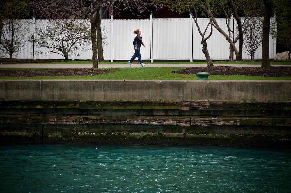 A woman jogging on the Chicago Riverwalk.<br /> <br /> The Chicago River system has seen dramatic improvements to water quality over the last few decades. Many sources of pollution have been eliminated, and remaining discharges are regulated by the City. Since chlorination of sewage effluent was stopped in the 80's, wildlife in the river has rebounded.<br /> <br /> Green Chicago..Photographer: Chris Maluszynski /MOMENT