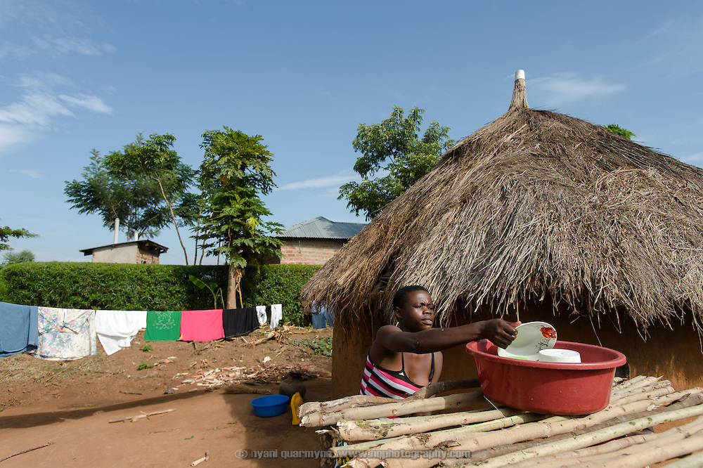 "Catherine Apoyo, an Afripads customer, doing the washing up at her home near Tororo, Uganda on 2 August 2014. She says, has been using Afripads for three months, and says of them ""It's very good. It's comfortable."" Previously she would use rags when she had her period, and said, ""Sometimes blood would come out onto my skirt, or they can even fall down when you are walking."" She would stay home from school at times, because she was not comfortable going out using rags."