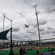 Student Ashleigh Blair dismounts from the bar at Trapeze School New York during the June 4th morning class. The two hour beginner session taught the nine students in attendance the basics of flying trapeze -- including knee hangs and backwards somersaults -- in their facility on the roof of Pier 40...CREDIT: Daniella Zalcman for The Wall Street Journal.SLUG: NYMETROMONEY_Trapeze