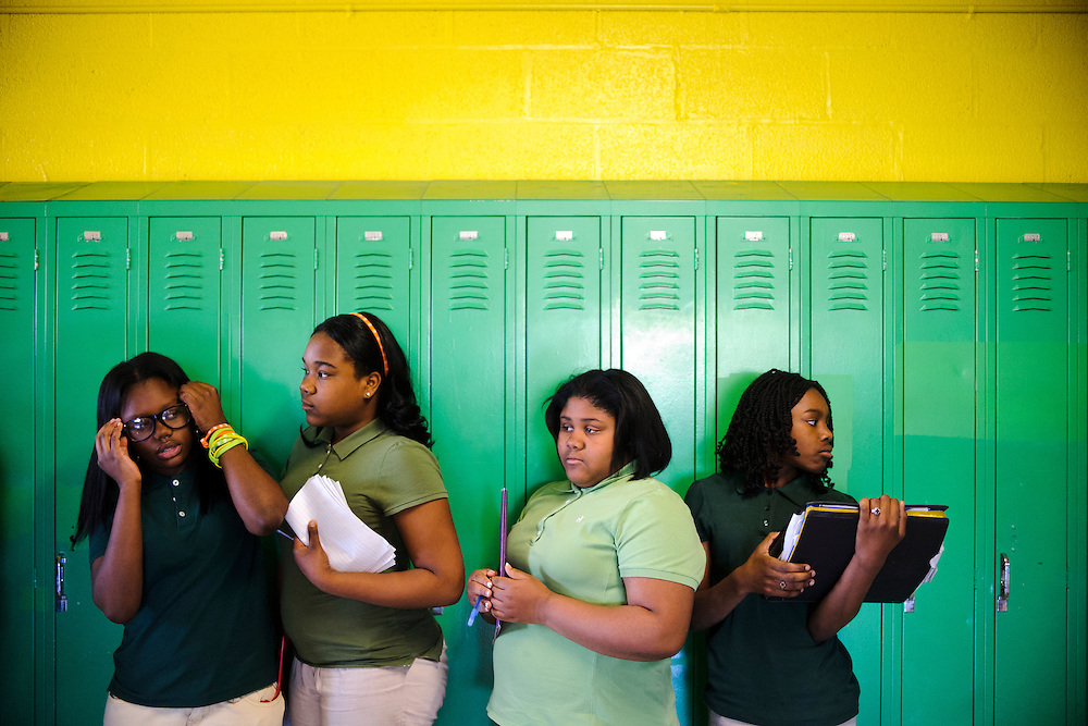 "Friendship Preparatory Academy seventh graders (L-R) Kendria Howard, Jazmean McFadden, Jasmine Dukes, and Tyanna Montgomery, wait in line between classes, Thursday, April 12, 2012...Baltimore City ""turnaround"" school Friendship Preparatory Academy Elementary and Middle, have benefited from the federal School Improvement Grant Program thanks to a partnership with the D.C.-based Friendship Public Charter School organization (NOTE: Friendship Prep is NOT a charter school, according to the vice principal). The school, which serves 98% of the students reduced and free lunches, used the grant money for improvements like buying technology, installing white boards, painting the hallways, replacing flooring, and paying for classroom libraries...Matt Roth For Education Week"