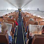 Two men sit side by side on an airplane in mid flight and read their newspapers to pass the time while flying.