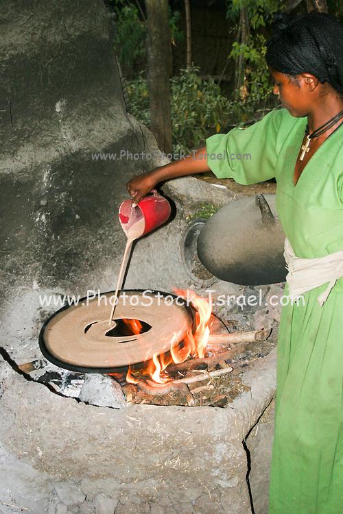 Africa, Ethiopia, Lalibela, Woman cooking Injera (pancake like bread) on a mogogo over a fire