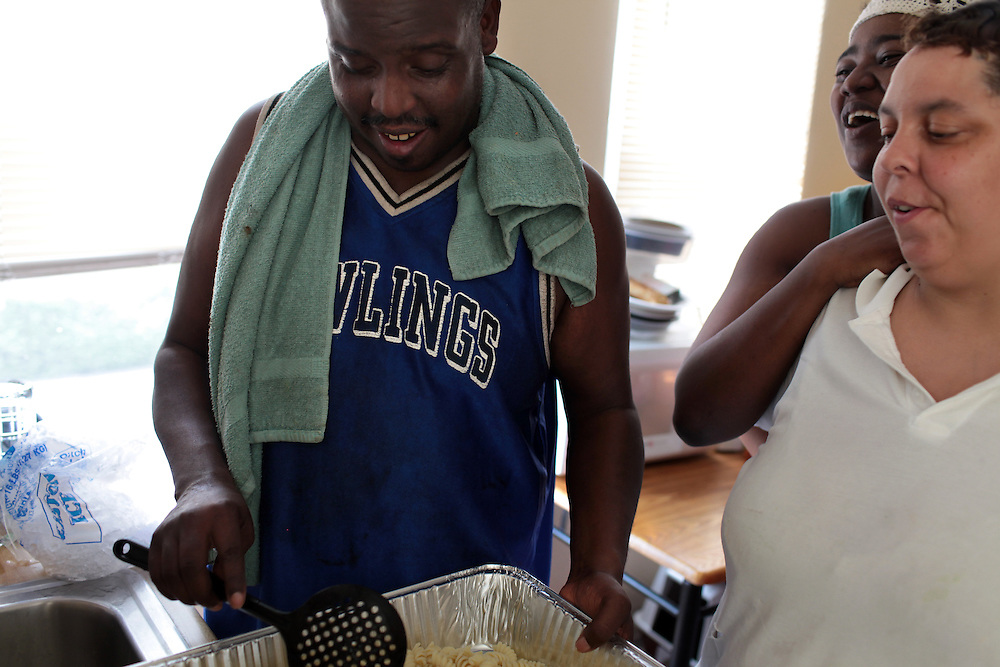 William Horne, left, cooks lunch for Salone Williams, 26, right, and Kimberly Robinson, far right, at his home in Baltimore, MD on August 8, 2010. William Horne lost his home in a rent-back scheme and is currently suing the company. For ProPublica on the Baltimore foreclosure story. .Photographer: Melanie Burford for ProPublica.