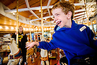 JEROME A. POLLOS/Press..Alex Hess, 8, takes a spin on the carousel at Riverfront Park in Spokane during a special outing for children in the Wishing Star Foundation. Hess, who has neurofibromatosis, is taking his first trip on an airplane today to visit his grandfather and spend time with his family. The trip is a wish granted by Wishing Star.