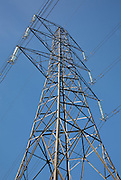 Looking up at an Electricity Pylon, carrying overhead power line with suspension tower design set against a blue sky at Ravensgate Hill in Gloucestershire, England.