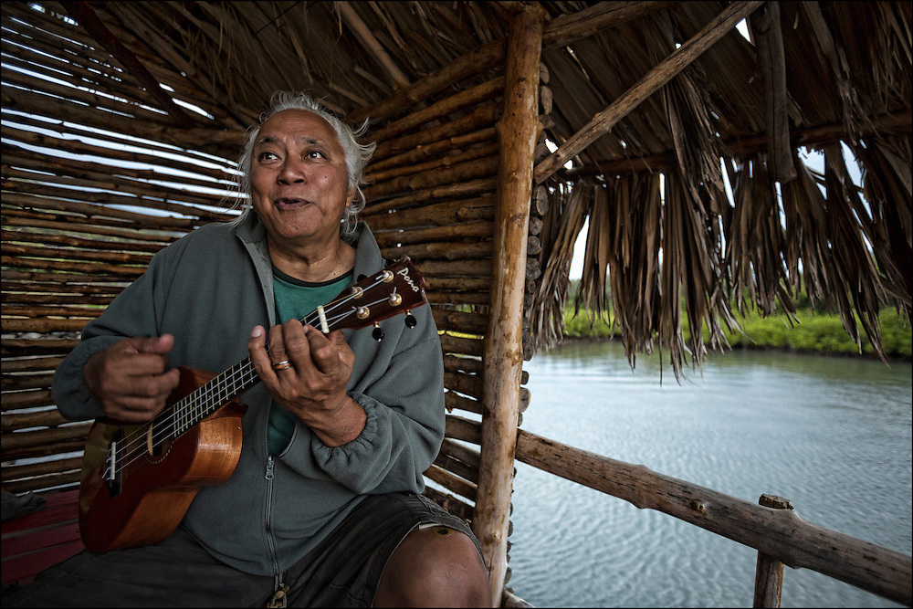 "Brother Nolan also referred to as ""Uncle No"" plays ukulele during sunset kanikapila at the Ho'ea Initiative base camp located at the Keawanui Fishpond on Molokai."