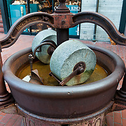 An old cocoa grinder with cast iron vat and two millstones is displaye at the famous Ghirardelli Square chocolate factory, in San Francisco, California, USA. The Old World knew nothing of chocolate prior to 1492. In 1519, Aztec Emperor Montezuma (Moctezuma) served chocolatl in golden goblets to conquistador Cortez in what would become Mexico.