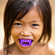 A Cambodian child Taunts the photographer with purple vampire teeth.