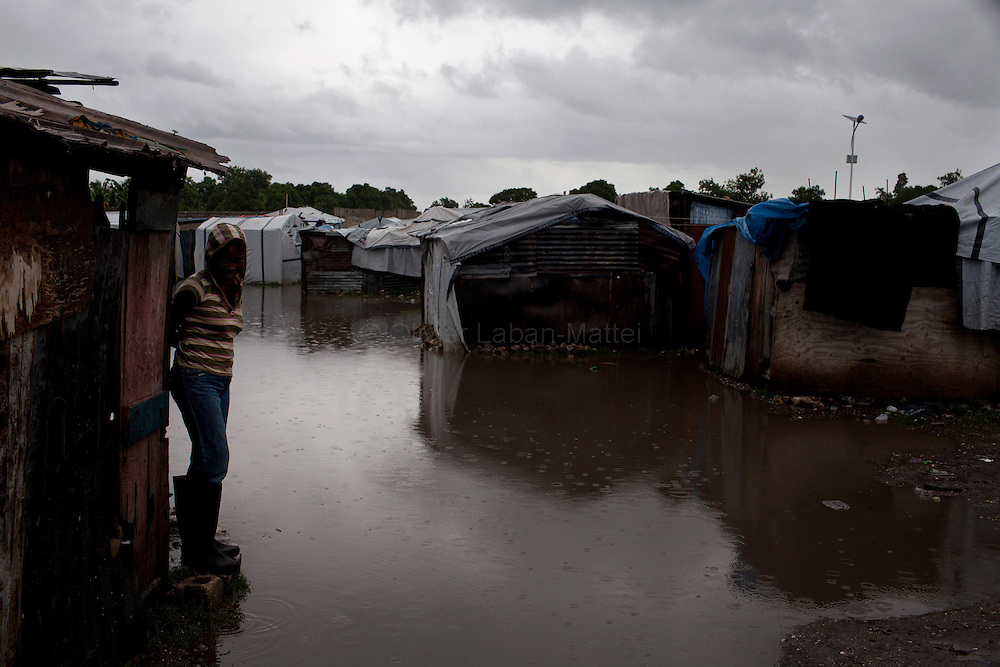 After hurricane Tomas went through Haiti, the city of Leogane has been totally flooded by the heavy rain and the overflow of the river Roullorne.///A young Haitian leaving in a refugee camp in Leogane since the earthquake in January, stays on her doorstep, during hurricane Tomas.