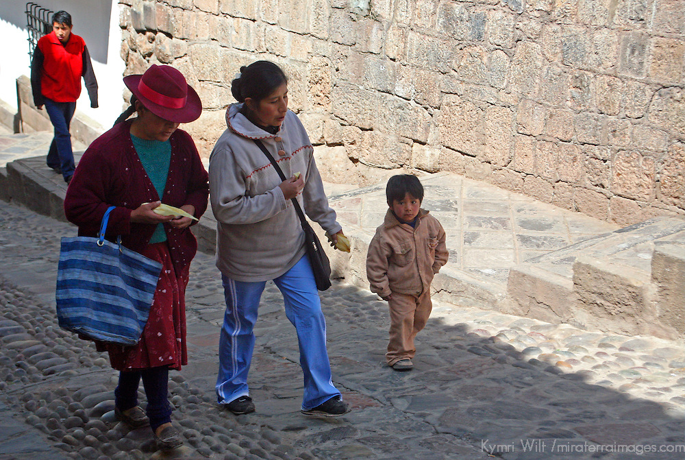 South America, Peru, Cusco. Locals walking one of the cobbled streets of Cusco.
