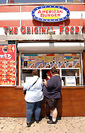 An overweight couple pick up their food at a hamburger stand on Venice Beach, CA on Friday, July 30, 2004.