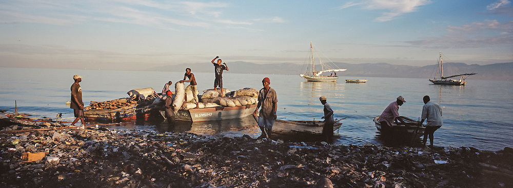 Fishermen get set to head out from the Carrefour area early in the morning as bags of charcoal are unloaded from another boat on Monday, December 15, 2014 in Port-au-Prince, Haiti.