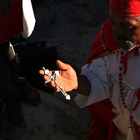 A healer and follower of Nino Fidencio, a curandero or healer who passed away in the 1938, conducts a healing session on top of a hill just outside of Espinazo, Mexico on October 18, 2006. Followers of Nino Fidencio believe that his spirit can posses other healers, who once possessed speak in a child like voice and perform a variety of medical cures on their followers. His believers, an estimated 20,000, gather in his hometown for a three-day festival twice a year in March and October. (Photo/Scott Dalton)