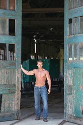 shirtless muscular man standing by large wooden doors