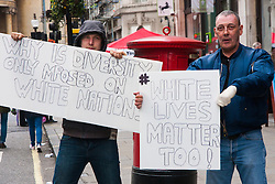 London, March 21st 2015. Thousands of people from across the UK march along Regent Street in the Stand Up To Racism protest. PICTURED A couple of far-right conter protesters express their views on diversity.