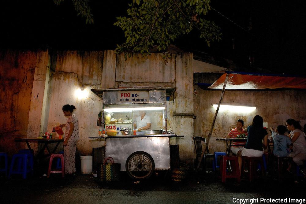 dining 'al fresco' at a one of saigon's many noodle carts, ho chi minh city, vietnam