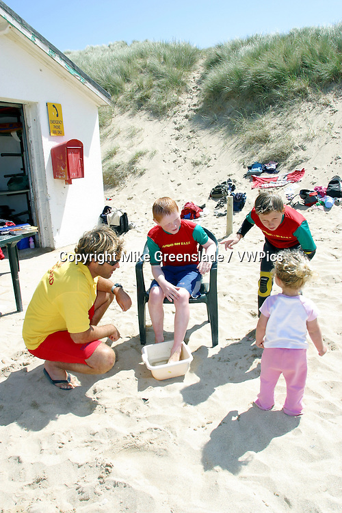 RNLI beach lifeguard treats a young member of Holywell Bay suf club for a weaver sting, Cornwall, UK