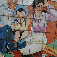 """A tiled mural in a Guangzhou street advocates """"happy families"""", and China's """"one child"""" policy for families, in a bid to control the growing population of the country."""
