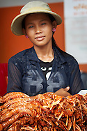 A Cambodian woman sells an aromatic pile of fresh-caught prawns near Phnom Penh, Cambodia. Fresh seafood is a staple of life in this Southeast Asian country.