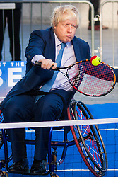 City Hall, London, November 24th 2014. Mayor Boris Johnsonwelcomes the world's best wheelchair tennis players with a game of mini tennis outside City Hall. The players are in London to compete in the NEC Wheelchair Tennis Masters 2014, being held at the Lee Valley Hockey and Tennis Centre, being held from 26 - 30 November. PICTURED: Mayor Boris Johnson rallies for wheelchair Tennis outside City Hall.