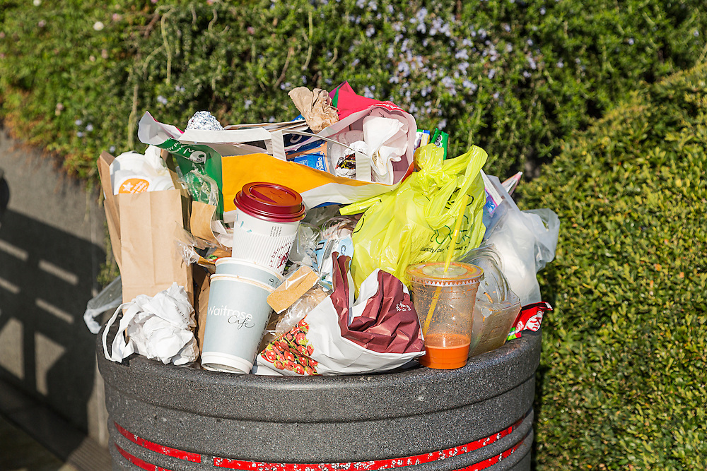 An overflowing rubbish bin containing the remnants of people's snacks and lunches. The bin contains plastic bags, food wrappers and disposible cups from various well known high street vendors.