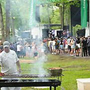 COLUMBIA, MD - May 11th, 2013 - A food vendor prepares food while the band Shark Week performs in the background at the 2013 Sweetlife Food and Music Festival at Merriweather Post Pavilion in Columbia, MD. (photo by Kyle Gustafson / For The Washington Post)