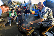 May 12, 2003 - Bible study and hot dogs make a good combination for dinner at Dignity Village in Portland, OR. Though the coals were too hot and the dogs began to burn forcing a quick turn with fingers earning a slight burn. There are now 65 homeless people who have taken up residence on the leaf recycling land near the airport with the city's permission. They are being asked to leave again by October and find a new home.