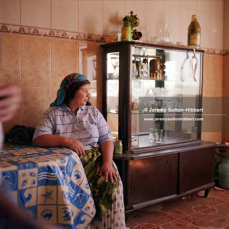 Miora Stanescu sits within the kitchen of her new home, built with the profits of scrap metal dealing, in the Roma community of Sintesti..