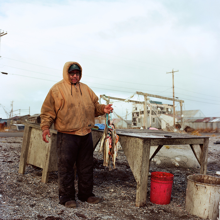 """""""Hardly anyone does this anymore. In the fall time they run thick—right now they are really healthy. We eat them half dried and frozen. I grew up eating this food."""" — Nick Topkok preparing his day's catch of tomcod fish for dying, on the beach in Teller, Alaska."""