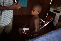 simpson a young boy from wangamalo is treated for a cut to his leg by lander at the wangamalo clinic. Treatment like this could prove vital because in the jungle small cuts can very quickly turn septic.