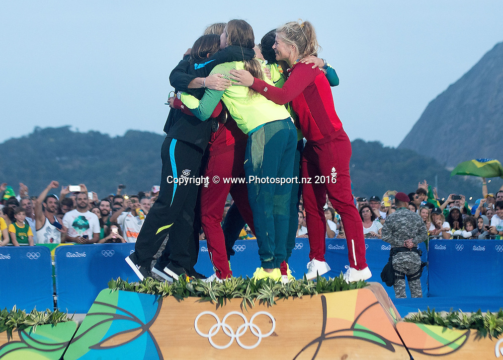 New Zealand's Alexandra Maloney<br /> and Molly Meech Silver, Brazil&rsquo;s Martine Grael and Kahena Kunze Gold and Denmark's Jena Hansen and  Katja Salskov-Iversen Bronze hug during the Women's 49fx class sailing race medal ceremony at the 2016 Rio Olympics on Thursday the 18th of August 2016. &copy; Copyright Photo by Marty Melville / www.Photosport.nz