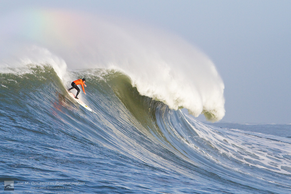 A surfer drops into a huge wave, under a rainbow, in the first heat of the 2010 Mavericks Surf Contest held in Half Moon Bay, California on February 13, 2010