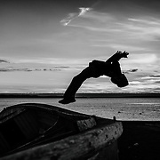 A young man doing back flip from the top of a wooden boat to the ground.
