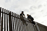 Migrants illegally climb a border fence into the United States from Mexicali, Mexico on Friday, April 14, 2006.<br />