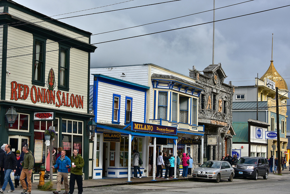 Historic Buildings on Broadway Avenue in Skagway, Alaska<br /> Skagway, Alaska, is a quiet town on the Inside Passage of the Pacific Ocean.  Many of its 100 historic buildings are managed by the National Park Service.  During the peak of the Klondike Gold Rush, its population ballooned to 30,000.  Today, less than 1,000 people live year round.  However, about 100 years after the last gold prospector, a new surge of adventurers started visiting from May through September: about one million tourists arrive each year by cruise ship for a few hour visit.