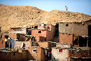 A boy runs along the Muqattam cliffs in the Manshiet Nasser slums on eastern outskirts of Cairo, Egypt, October 5, 2011. Along with the threat of another rock slide, residents live without basic public services such as water supply and waste management. Ann Hermes/© The Christian Science Monitor 2011