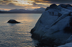 The sun sets on Muir Inlet and rocks in this image take near the Klotz Hills in Glacier Bay National Park and Preserve in southeast Alaska.
