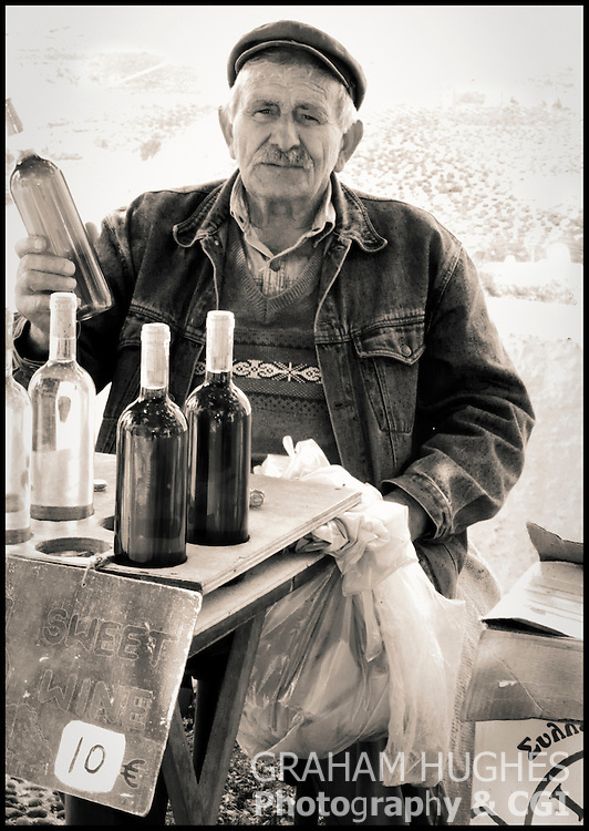 Man selling home made wine in village in Santorini, Greece.