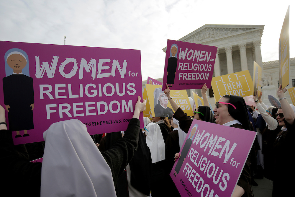 Protesters demonstrate before Zubik v. Burwell, an appeal brought by Christian groups demanding full exemption from the requirement to provide insurance covering contraception under the Affordable Care Act, is heard by the U.S. Supreme Court in Washington March 23, 2016.      REUTERS/Joshua Roberts