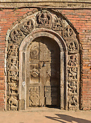 """Religious deities and symbols are carved in an ancient wood doorway in Patan's Durbar Square, Nepal, Asia. Patan was probably founded by King Veer Deva in 299 AD from a much older settlement. Patan, officially called Lalitpur, the oldest city in the Kathmandu Valley, is separated from Kathmandu and Bhaktapur by rivers. Patan (population 190,000 in 2006) is the fourth largest city of Nepal, after Kathmandu, Biratnagar and Pokhara. The Newar people, the earliest known natives of the Kathmandu Valley, call Patan by the name """"Yala""""  (from King Yalamber) in their Nepal Bhasa language. UNESCO honored Patan's Durbar Square (Palace Square) as one of the seven monument zones of Kathmandu Valley on their World Heritage List in 1979. All sites are protected under Nepal's Monuments Preservation Act of 1956."""