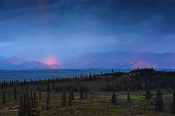 The last remnants of a late evening rainbow appears before a completely cloud shrouded Mt. McKinley in Denali National Park and Preserve in Alaska. The view is from the Wonder Lake campground. The visible mountains are the foothills of the Alaska Range.