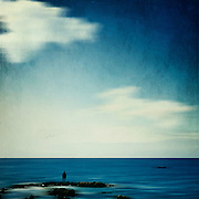 Abstraction of a person standing on rocks staring at the sea.
