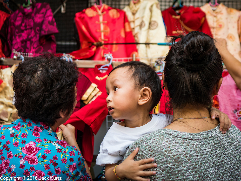 "03 FEBRUARY 2016 - BANGKOK, THAILAND:  Women shop for new traditional Chinese dresses before Chinese New Year in Bangkok. Thailand has the largest overseas Chinese population in the world; about 14 percent of Thais are of Chinese ancestry and some Chinese holidays, especially Chinese New Year, are widely celebrated in Thailand. Chinese New Year, also called Lunar New Year or Tet (in Vietnamese communities) starts Monday February 8. The coming year will be the ""Year of the Monkey.""            PHOTO BY JACK KURTZ"