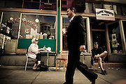 A man in a black suit walks by patrons of Caffe Trieste in North Beach, San Francisco, California, USA.