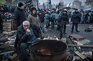 Protesters and Berkut officers stand at the spot of an  encampment that was stormed by the riot police outside the Trade Union building after an early morning crackdown by authorities that partially clear Maidan Square of anti-government protesters. Later in the day, all police units withdraw from inside Maidan square. on December 11, 2013 in Kiev, Ukraine. Thousands have been protesting against the Ukrainian government after Ukrainian President Viktor Yanukovych decided to suspend a trade and partnership agreement with the European Union in favor of incentives from Russia.