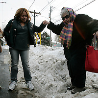 Belmont, MA -  Yelitza Hernandez (C) of Belmont lends a hand to 76 year old Nancy Keill of Belmont as she tried to step off the sidewalk over a snow mound so she could wait for the73  bus on the street on January 28, 2010.  Looking on is Carmen Gonzales of Belmont (L).  Photo by Matthew Healey